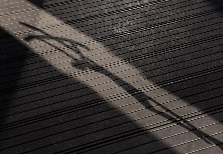 Schatten eines Kruzifixes fällt auf den Boden.