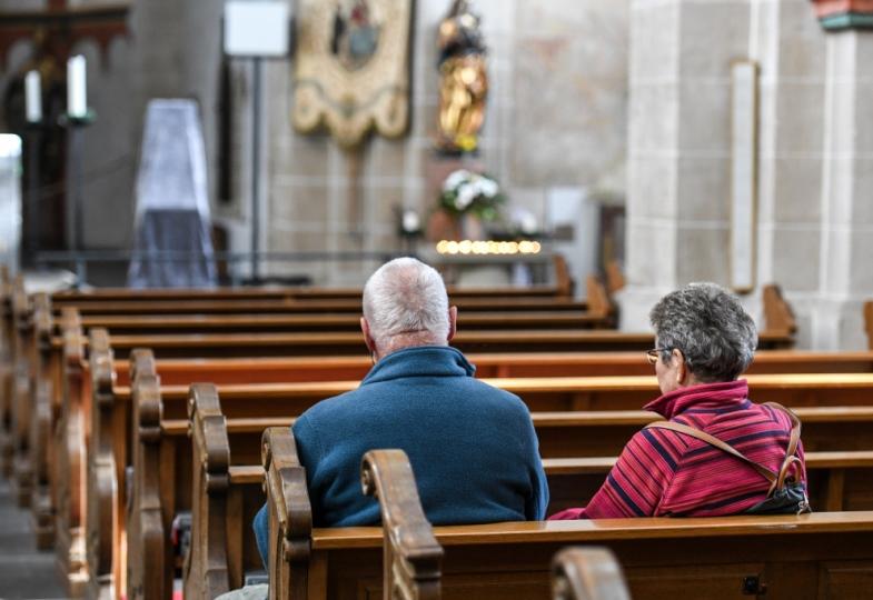 Ein Mann und eine Frau sitzen in einer Kirche.