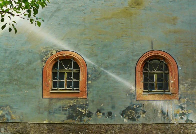 Eine Hausfassade mit zwei Fenstern wird von einem Sonnenstrahl getroffen.