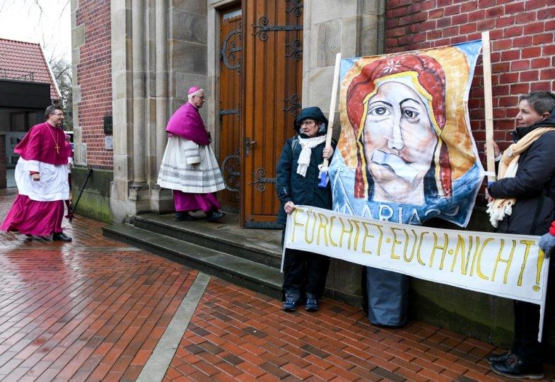 Frauen demonstrieren vor einer Kirche für mehr Partizpation.