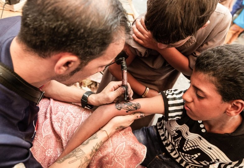 Tätowierer sticht einem Jungen ein Tattoo der Jungfrau Maria.