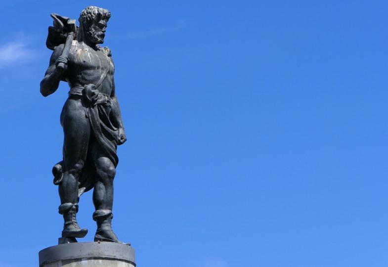 Eine Statue des Gottes Thor vor blauem Himmel.