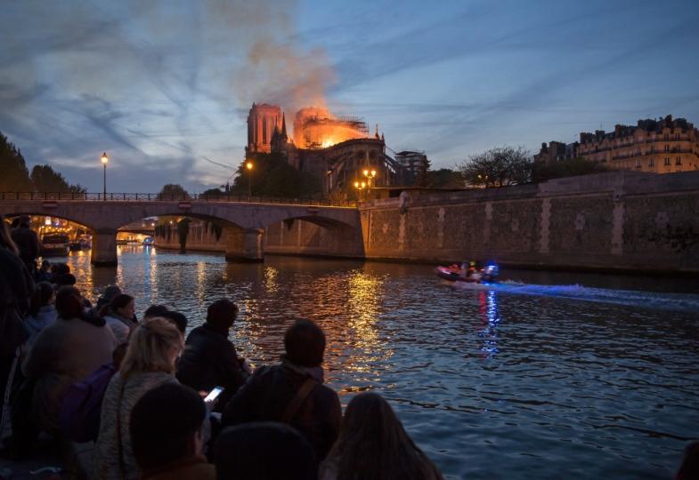 Menschen beobachten von einer Brücke den Brand der Pariser Kathedrale Notre Dame.