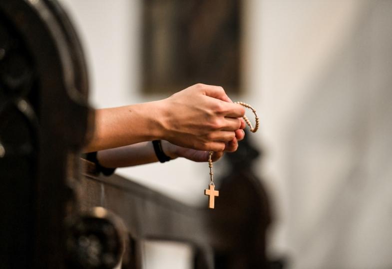 Gefaltete Hände halten einen Rosenkranz.