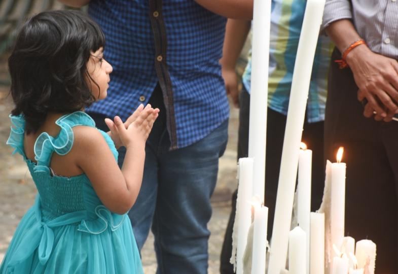 Ein kleines Mädchen aus Sri Lanka betet vor einigen Kerzen.
