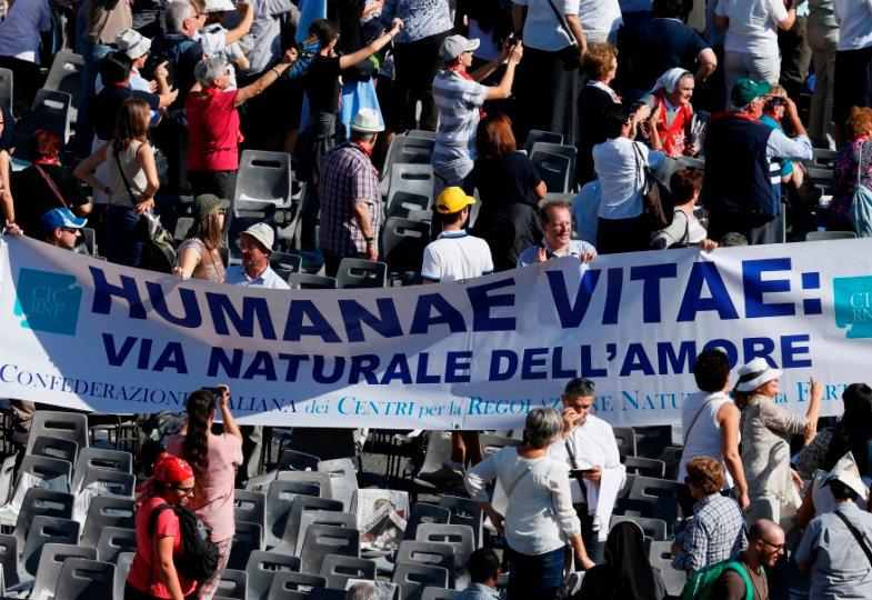 Menschen auf dem Petersplatz halten ein Plakat mit der Aufschrift