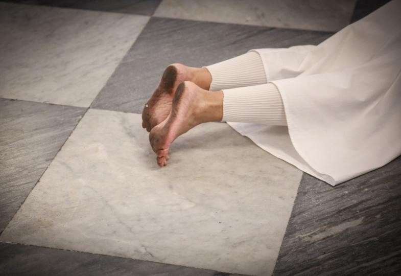 Ein Mensch mit nackten schmutzigen Füßen liegt bäuchlings auf dem Boden.
