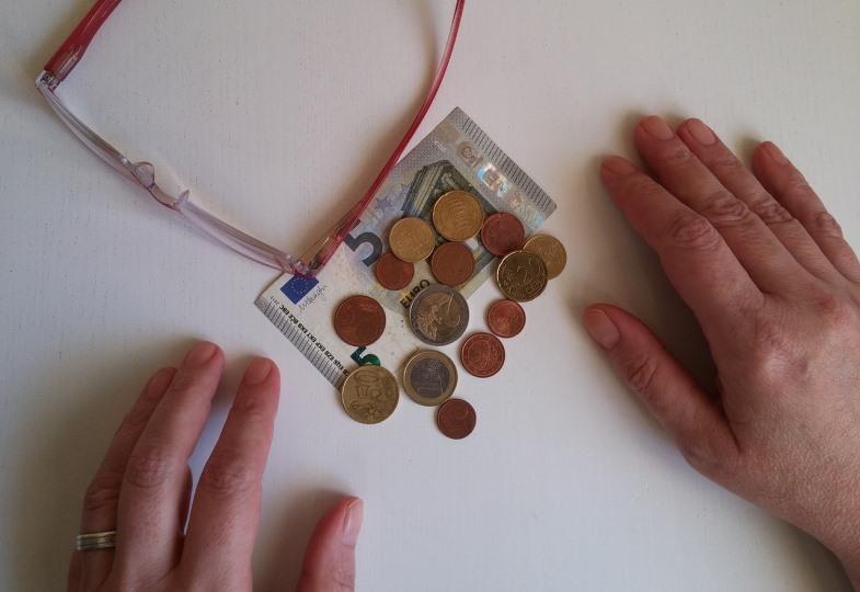 Hände, die eine kleine Summe Geld in Münzen und Scheinen abzählen.