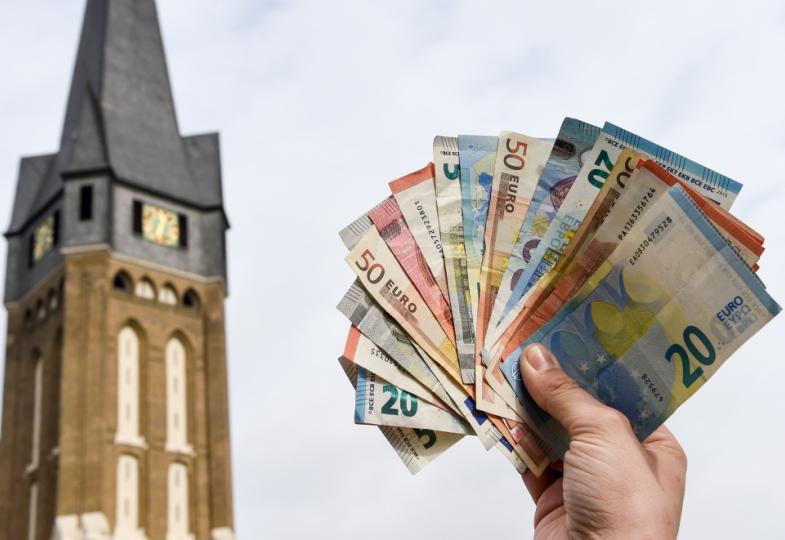 Eine Hand hält ein Bündel Geldscheine neben einem Kirchturm in die Luft.