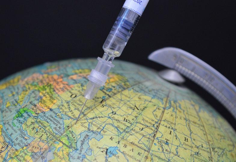 Weltkugel mit Impfspritze
