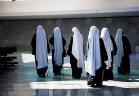 Mehrere Nonnen laufen durch eine Kirche