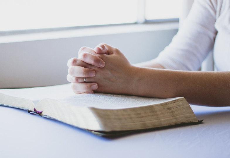 Betende Hände auf einem Buch