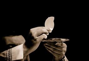 Ein Priester hält das eucharistische Brot