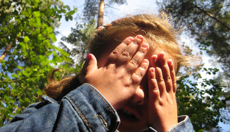Mädchen mit Händen vor Augen